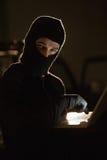 Pirata informático que usa el ordenador portátil para robar identidad Foto de archivo