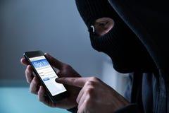 Pirata informático que usa el teléfono elegante para robar datos foto de archivo libre de regalías