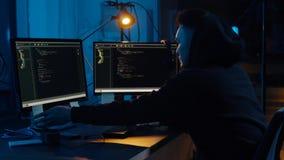 Pirata informático usando los ordenadores para el ataque cibernético en la noche almacen de video