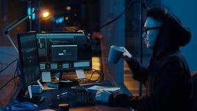 Pirata inform?tico que usa el ordenador para el ataque cibern?tico en la noche metrajes