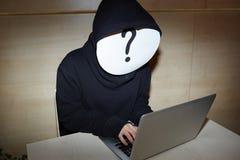 Pirata informatico anonimo con il computer portatile Fotografie Stock Libere da Diritti