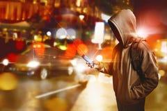 Pirata informatico anonimo facendo uso dello smartphone sulla via fotografie stock