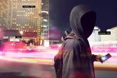 Pirata informatico anonimo facendo uso dello smartphone sulla via immagini stock