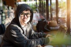 Pirata informatico asiatico nel codice fendentesi del cappuccio facendo uso del computer portatile e dei computer dentro Immagini Stock Libere da Diritti