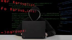 Pirata informatico in cappuccio nero con un computer portatile stock footage