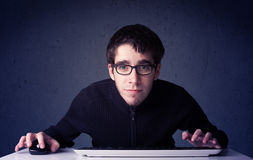 Pirata informatico che lavora con la tastiera su fondo blu Fotografia Stock Libera da Diritti