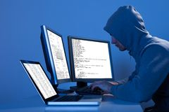 Pirata informatico che per mezzo dei computer multipli per rubare i dati Fotografie Stock