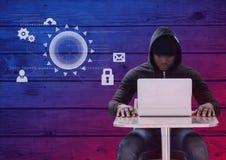 Pirata informatico che per mezzo di un computer portatile davanti a fondo di legno con le icone digitali Fotografia Stock Libera da Diritti