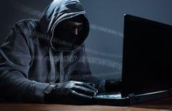 Pirata informatico che ruba i dati da un computer portatile Fotografie Stock