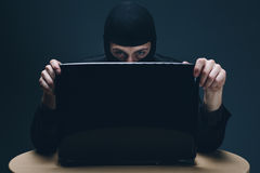 Pirata informatico che ruba i dati fuori da un computer portatile Fotografie Stock Libere da Diritti