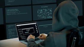 Pirata informatico che scrive sul computer portatile nella stanza del monitor L'uomo in cappuccio si siede alla tavola Schermo de archivi video