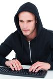 Pirata informatico concentrato che scrive sulla tastiera Fotografie Stock