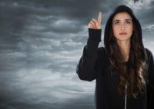 Pirata informatico della donna che alza il suo dito davanti a fondo nuvoloso Immagini Stock