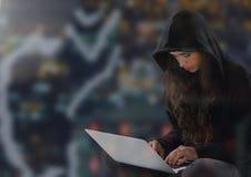 Pirata informatico della donna con le gambe attraversate facendo uso di un computer portatile Fotografie Stock