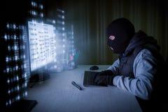 Pirata informatico di computer che ruba i dati da un computer Immagine Stock