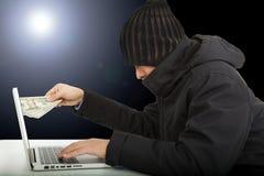 Pirata informatico di computer che ruba soldi nell'oscurità Fotografia Stock