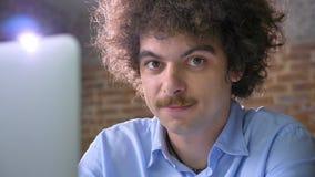 Pirata informatico divertente del nerd che scrive sul computer portatile e che esamina macchina fotografica che sorride, fondo de stock footage