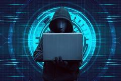 Pirata informatico incappucciato che scrive sul computer portatile mentre stando Fotografia Stock
