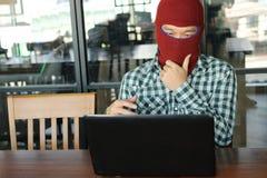 Pirata informatico mascherato che porta una passamontagna che guarda un computer portatile e che ruba i dati di informazioni impo fotografia stock libera da diritti