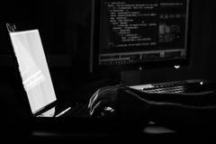 Pirata informatico russo che incide il server nello scuro in bianco e nero Fotografie Stock Libere da Diritti