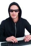 Pirata informatico severo con gli occhiali da sole che scrive sulla tastiera Fotografia Stock