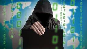 Pirata informatico in un cappuccio con il computer portatile Il pericolo online della rete Fotografia Stock