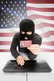 Pirata informático con la bandera en el fondo que sostiene la tarjeta de la identificación disponible - Estados Unidos Imagenes de archivo