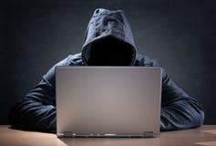Pirata informático de ordenador que roba datos de un ordenador portátil Imagen de archivo libre de regalías