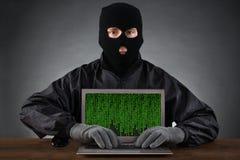 Pirata informático que mecanografía en el ordenador portátil con código binario Foto de archivo libre de regalías