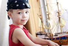 Pirate. Portrait of little pirate with model ship Royalty Free Stock Photography