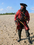 Pirate on the Beach in vintage costume. A pirate in vintage costume with weapons looks out to sea from the beach stock images