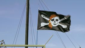 Pirate black flag, jolly roger, flutters in the wind near the mast of a moored ship. On a blue sky background stock video