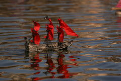 Pirate boat with red sails. Small remoted boad with red sails reflected on water a child toy to play with pirates Stock Images