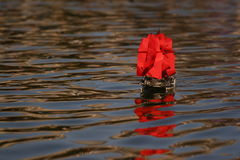 Pirate boat with red sails. Small remoted boad with red sails reflected on water a child toy to play with pirates Stock Photography