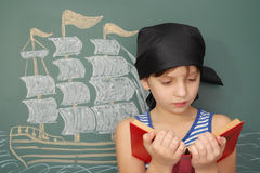 Pirate. Boy pirate with book and chalk drawing of ship Royalty Free Stock Image