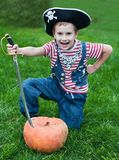 Pirate-boy and halloween pumpkin. Boy wearing pirate costume attacks pumpkin with sword Stock Images