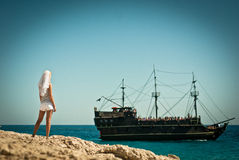 Pirate bride. Beautiful girl in a veil standing on the beach and looks into the distance to the ship Royalty Free Stock Photo