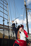 Pirate captain on ship shouts and waves sword Stock Photography