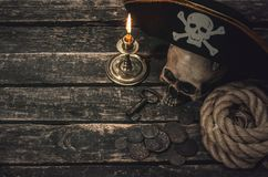 Pirate. Pirate captain table with pirate hat, human skull, treasure coins, mooring rope, burning candle and the key from treasure chest. Treasure hunter concept royalty free stock photography
