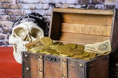 Pirate Chest and Gold Coins. Human skull with black skull cap next to wood chest full of gold coins and old paper money on red with brick wall background stock photos
