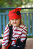 Pirate child. Portrait of cute little girl dressed up as a fierce pirate and looking shyly at the camera stock photos