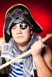 Pirate with a cocked hat and a rope. The actor in a suit of the pirate with a cocked hat and a rope on a red background Royalty Free Stock Image