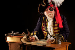 Pirate drawing a treasure map. Colorful gray bearded pirate captain sits at his desk, drawing a treasure map with a feather quill pen. His musket, a thick Royalty Free Stock Photography
