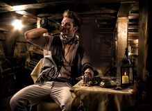 Pirate Drinking from Bottle in Ship Quarters. Handsome Rugged Male Pirate Drinking from Bottle in Ship Quarters Stock Photo