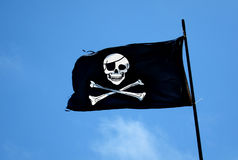 Pirate Flag. A black Pirate flag with a white skull flapping in the wind Royalty Free Stock Photo