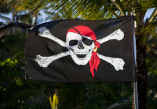 Pirate Flag. A black and red pirate flag waving in the wind stock photography