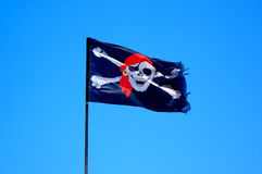 Pirate Flag. A black Pirate flag with a white skull and red headband flapping in the wind Royalty Free Stock Images