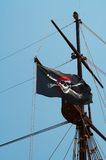Pirate flag. Waving pirate flag on the mast Stock Photo