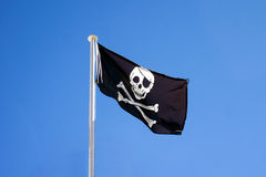 Pirate Flag In Blue Sky Background. A black Pirate flag with a white skull flapping in the wind in bright blue sky background Stock Photo
