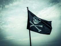 Pirate flag depicting a skull-and-crossbones. Photo shows a pirate flag depicting a skull-and-crossbones with stormy cloudy sky at the background Royalty Free Stock Images